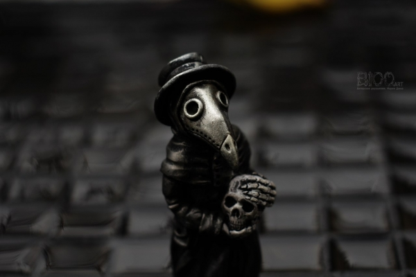 Чумной доктор, держащий в руках череп.
